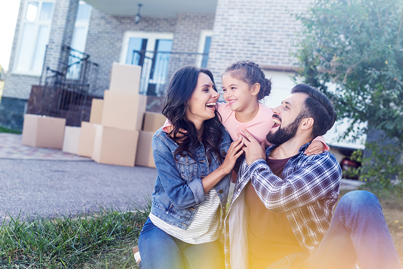 Mother and Father smiling, with arms around their daughter in front of moving boxes and their new home after receiving a home inspection