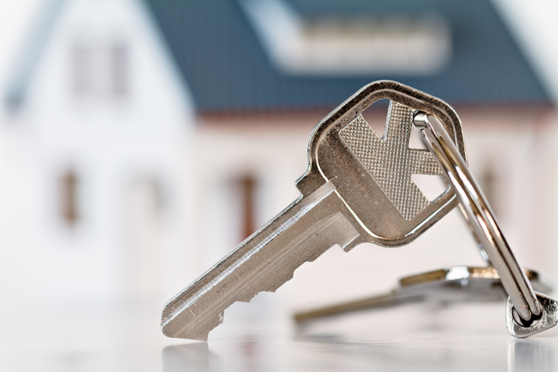 Keys in front of a house before a home inspection