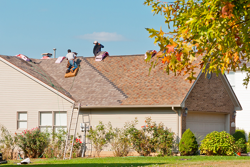 Roofers repairing the roof of a house in the suburbs after maintenance needs were discovered while home inspection services were being performed